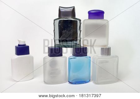 piramid of empty bottles of lotions after shave and a bottle of gel with dispenser