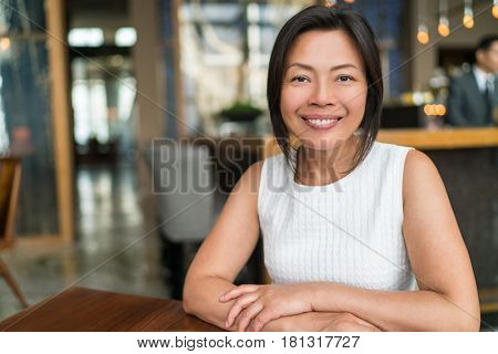 Happy elegant Asian middle-aged businesswoman smiling portrait. Beautiful mature Chinese business woman in fancy restaurant,