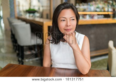 Elegant Asian middle-aged businesswoman pensive portrait. Beautiful mature Chinese business woman relaxing in restaurant bar urban stylish living,
