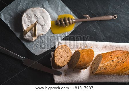 Brie cheese, pieces of baguette, honey on parchment horizontal