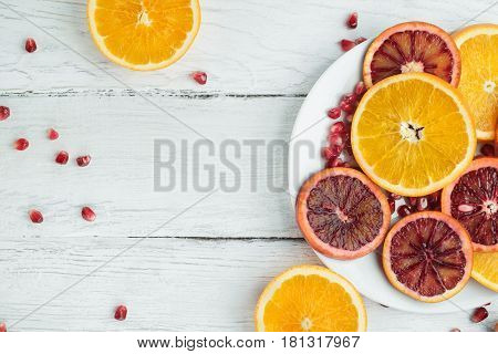 Slices of sicilian orange and common orange on a white wooden table. Pomegranate seeds scattered on a table. Top view. Space for text.