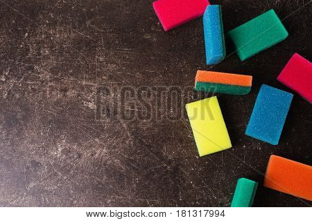 Colored sponges against dark marble background. Items for hygiene and washing dishes.Object on a dark background. Transparent object. Conceptual object. The objects are on the table. The object is on marble. The object lies on the surface