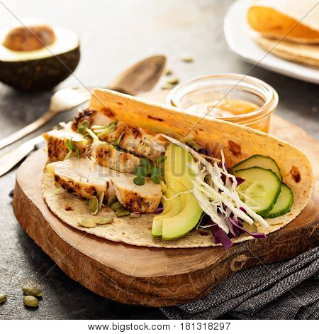 Making tacos with fresh vegetables, grilled chicken and avocado