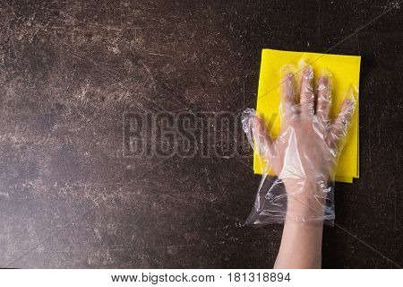 A hand with a rag on a dark marble background. Tidy up the house. Putting things in order. Object on a dark background. Transparent object. Conceptual object. The objects are on the table. The object is on marble. The object lies on the surface