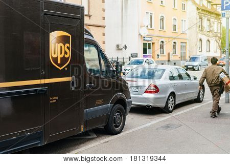 KEHL GERMANY - APR 6 2017: UPS United Parcel Service worker leaving the brown van delivery UPS truck parked on a street to deliver the parcel to the client