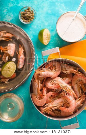 Casserole with shrimps, capers, lime, sauce on the table vertical