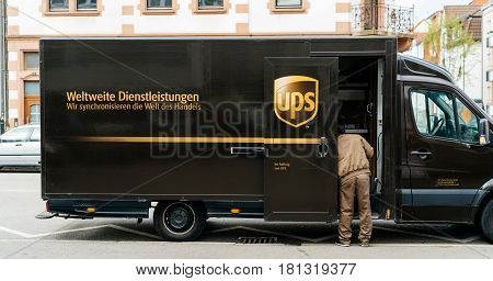 KEHL GERMANY - APR 6 2017: UPS United Parcel Service van delivery brown UPS van parked on a street with driver worker searching for the parcel in the van interior