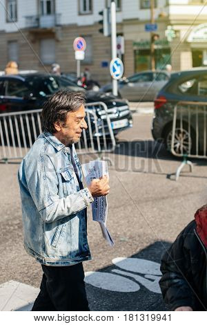 STRASBOURG FRANCE - APR 8 2017: Political agitation at French market for the upcoming French presidential election 2017 - Parti ouvrier independant newspaper distribution by man