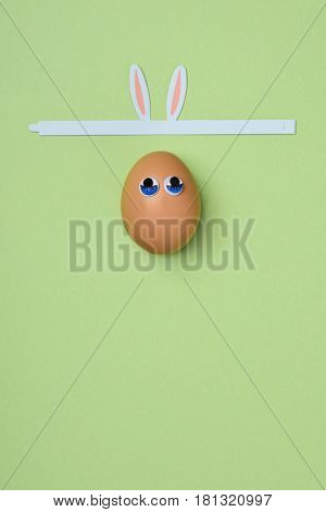 brown egg with a pair of three-dimensional eyes and a band with rabbit ears on a green background, with a blank space on the bottom