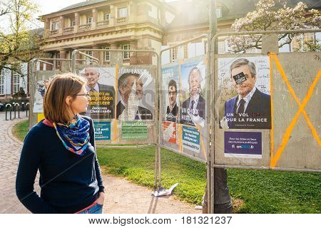 STRASBOURG FRANCE - APR 12 2017: Woman looking at official campaign posters of Francois Fillon and other political party leaders of eleven candidates running in the 2017 French presidential election