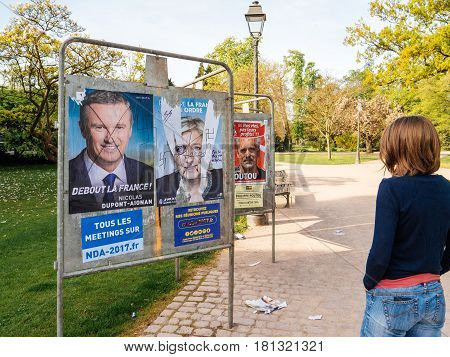 STRASBOURG FRANCE - APR 12 2017: Woman looking at official campaign posters of Marine Le Pen political party leaders ones of the eleven candidates running in the 2017 French presidential election