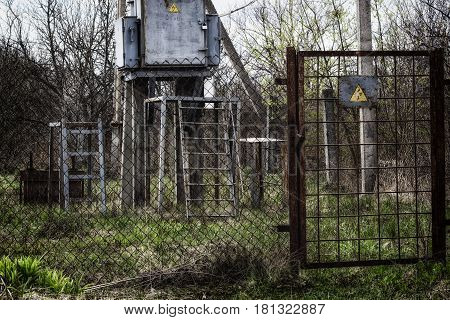 Cautiously high voltage transformer fenced with metal mesh door with grilles warning sign dangerous to life