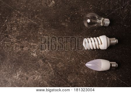LED bulb, incandescent lamp, fluorescent lamp on a dark marble background. To save energy. Eco concept