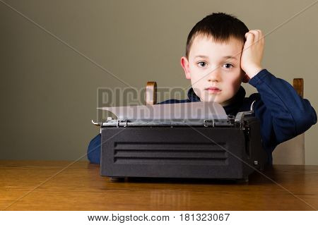 Cute little boy looking distracted in front of a vintage black typewriter at home