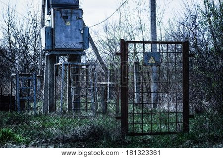 Warning triangular sign on a rusty grill door hanging lock dangerous for life high voltage current passing