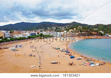 Tossa de Mar, Spain - August 12, 2010: Beach with people at Tossa de Mar at the Costa Brava at the Mediterranean Sea in Spain.