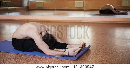 Young smart man trains in the hall for training. Tight body. Morning work-out. Do sport. The trainer in the sport form. Sport concept