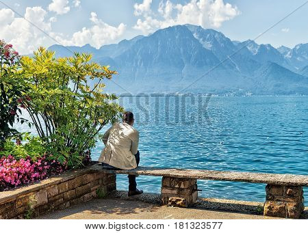 Montreux, Switzerland - August 30, 2016: Man sitting on the bench on the embankment of Geneva Lake in Montreux Vaud canton Switzerland
