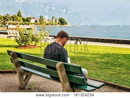 Vevey, Switzerland - August 30, 2016: Man sitting on the bench at the embankment on Geneva Lake in Vevey Vaud canton Switzerland