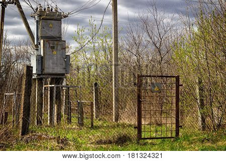 Transformer under the gray sky high voltage is dangerous for life the sign warns the territory is fenced current passes