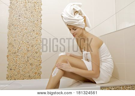 Young adult woman applying moisturizer cream on the legs in bathroom