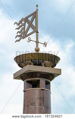 The weather vane, stylized Russian St. Andrew's flag on the top of a tall tower on blue sky background