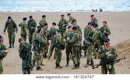 Saint Petersburg, Russia - August 9, 2015: a group of officers and soldiers of the marine corps of the Russian army in a protective camouflage stand on a sandy shore, after performing the training tasks