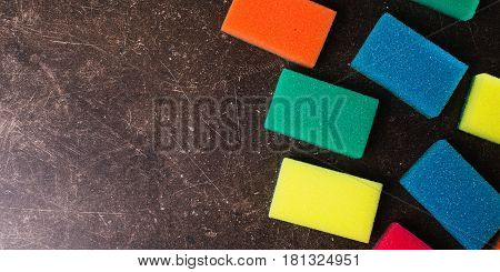 Colored sponges against dark marble background. Items for hygiene and washing dishes. Sponges concept. Sponges on table