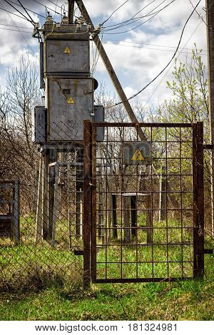 Transformer under the blue sky iron locker under the lock above it wires passes current high voltage is very dangerous fence warning sign