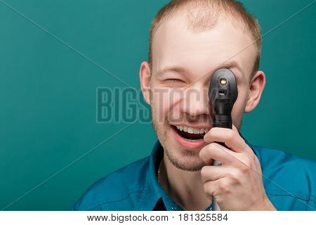 optometrist with ophthalmoscope, instrument to look into eyes by doctor on the blue background