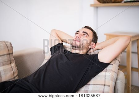 Man With Hands Behind Head Lying On Sofa At Home