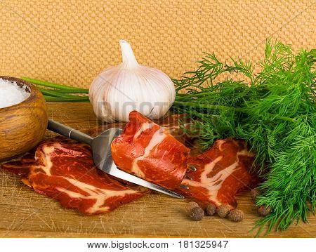 Country still life with bacon with pepper on wooden plate