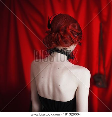 Beautiful back hairstyle with feathers. Woman with red curly hair in a black dress and retro makeup on a red background. Red-haired girl with pale skin bright unusual appearance. Noir woman