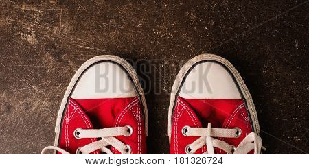 Red sneakers on a dark marble background. Footwear for outdoor activities. Footwear for sport. New footwear