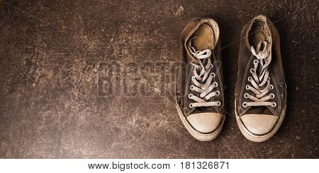 Old black sneakers on a dark marble background. Footwear for outdoor activities, Sneakers for sport. Sneakers concept