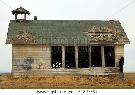 Abandoned Country Schoolhouse in Disrepair with Vacant Windows and Torn Roof
