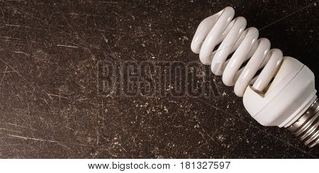 Fluorescent light bulb poster on a dark marble background. To save energy. Eco poster concept