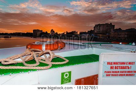 Lifebuoy with line and rope on the ship at sunset and clouds
