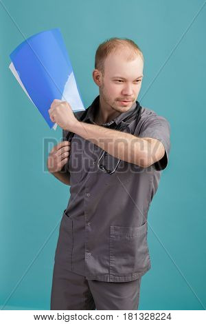 angry young male doctor holding a folder with papers on the blue background