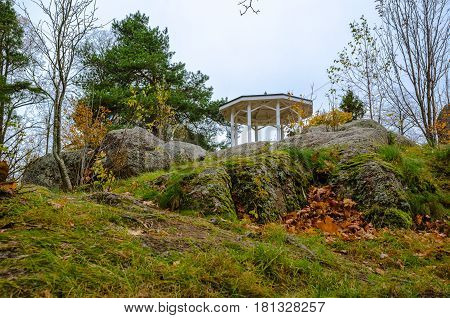 Gazebo on a small hill covered with rocks and moss