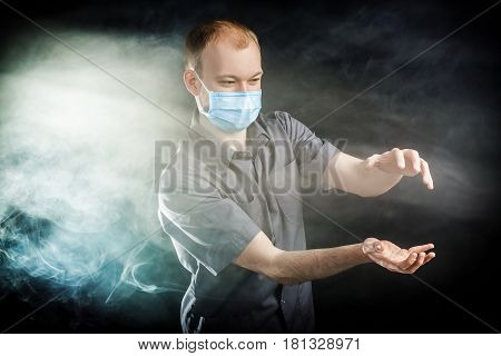 young doctor in a mask in the smoke