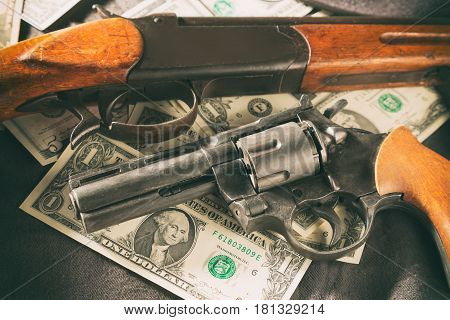 Mafia concept. Black gun with shotgun on dollar banknotes. Toned image.
