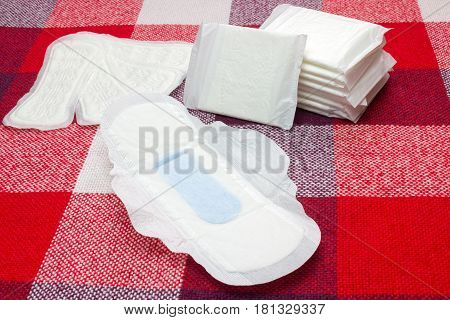 Menstruation sanitary pads and cotton tampons for woman hygiene protection. Soft tender protection for woman critical days gynecological menstruation cycle. Tampons and pads on the plaid at home