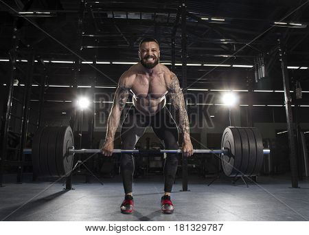 Attractive Muscular Bodybuilder Doing Heavy Deadlift Exercise In