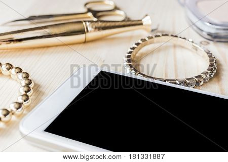 White mobile phone, gold bracelet, bracelet with large stones, gold manicure scissors, mascara in a gold tube, powder on a light wooden background. Women's tricks concept