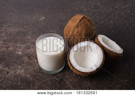 Coconuts and coconut milk on a dark marble background. Personal care. Spa treatments. Coconut milk concept