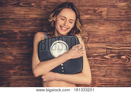 Beautiful young woman in sportswear is hugging weigh scales and smiling on wooden background