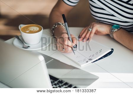 Close up portrait of a woman's hands writing a letter or making notes.
