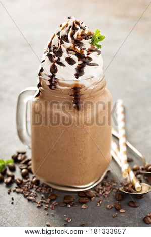 Chocolate frappe coffee with whipped cream and syrup on light background