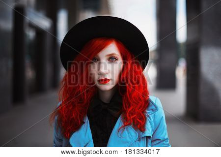 Woman with red curly hair in blue coat on background of big city. Red-haired girl with pale skin and bright appearance with black hat on head. Street style